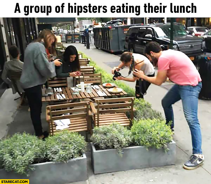 A group of hipsters eating their lunch taking photos instead of eating