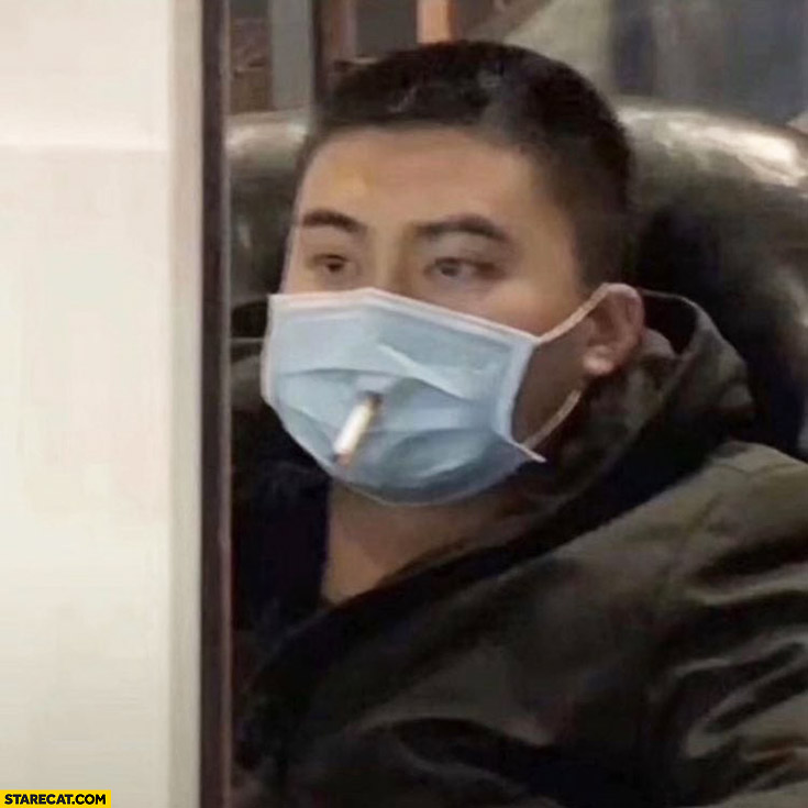 Chinese man smoking a cigarette through hole in face mask