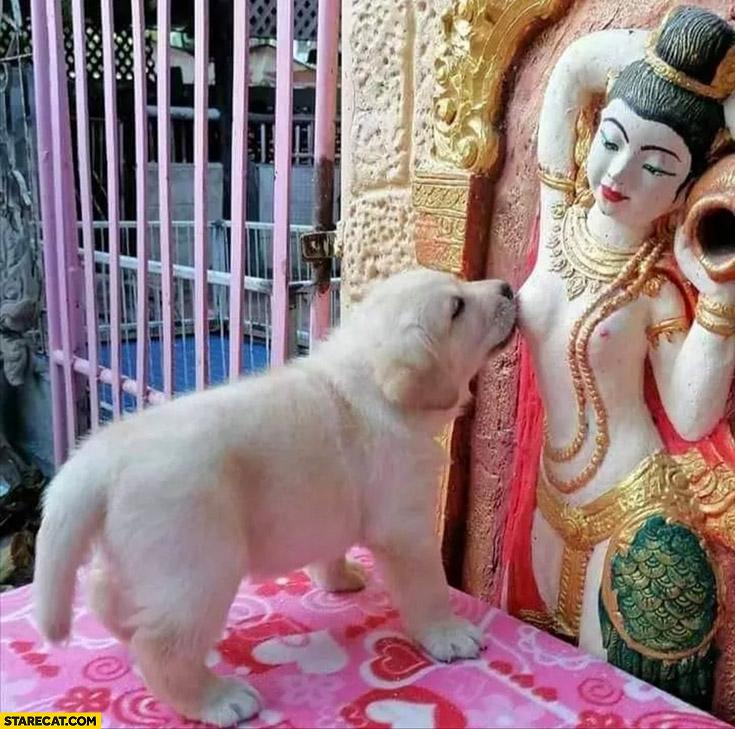 Cute puppy licking woman sculpture