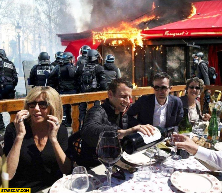 Macron having a nice dinner while his country is in chaos police in background
