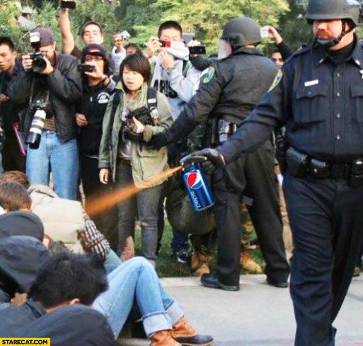 Policeman using pepper gas spray Pepsi can protesters ad