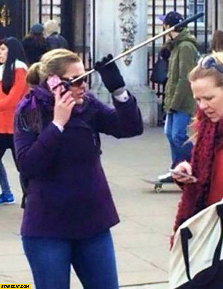 Woman talking on the phone with selfie stick attached